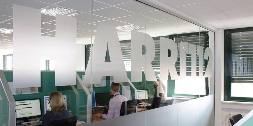 Angestellte sitzen hinter einer Glasscheibe, auf der das Harri-Logo groß aufgebracht ist.