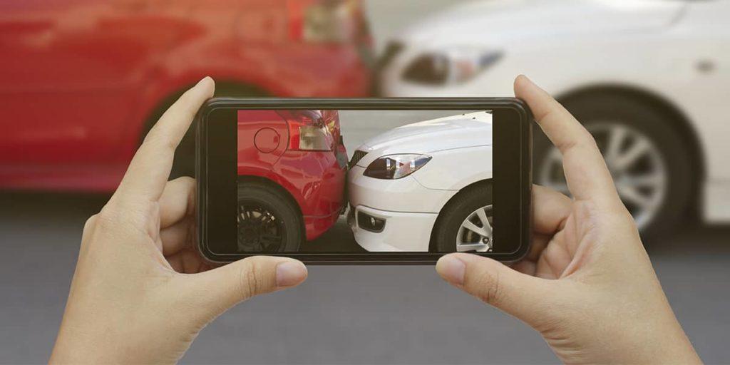 Eine Person macht mit Ihrem Smartphone Fotos vom Schaden, nachdem sie einen Unfall hatte.